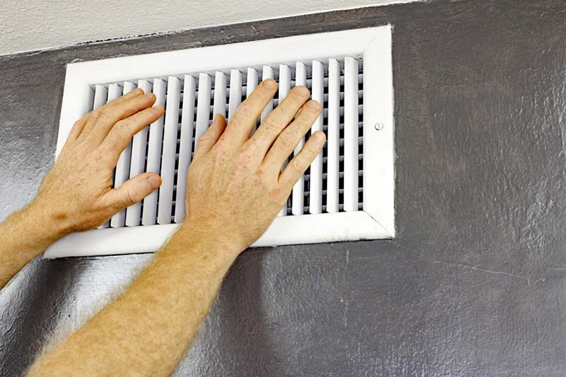 Hands feeling hot air blow out of white vent