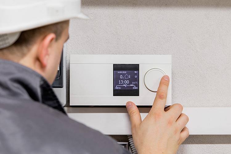 man in white hard hat adjusting thermostat