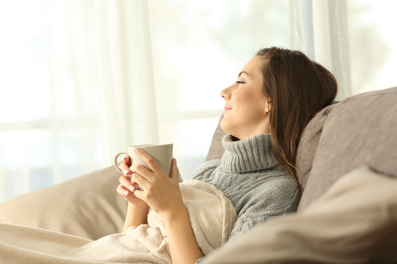 Portrait of a pensive woman relaxing sitting on a sofa in the living room in a house interior in winter enjoying her zone control system.